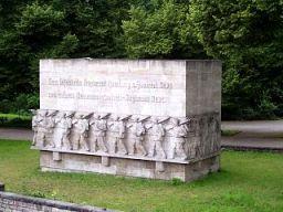 Ein Foto des Denkmals für das 76. Hamburger Infanterieregiment, ein sehr großer Betonquader mit den Reliefs von marschierenden Soldaten ringsum, auf einer Wiese stehend.