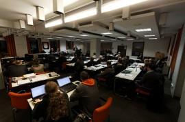 In einem schlecht beleuchteten, gedrungenen Raum sitzen Menschen zu einem Podium gerichtet an Tischen, auf denen sie Computer und Unterlagen vor sich haben. Säulen durchteilen den Raum und verschlechtern die Sicht.