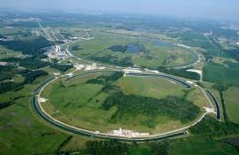 Luftbild des Fermilab-Forschungszentrums, große ringförmige Betonstrukturen in einer grünen Landschaft.