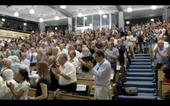 Ein Hörsaal voller stehen applaudierender Menschen.