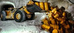 Ein flacher, großer Schaufelbagger steht in einem Bergwerksschacht und kippt gelbe Fässer auf einem Haufen zusammen.