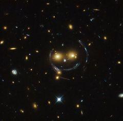 """Smile! Die """"Gesichtszüge"""" dieses Galaxienclusters in einem Hubble-Foto sind verzerrte Bilder dahinter liegender Galaxien."""